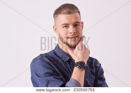 Close up of attractive bearded hipster touching chin with hand and smiling while isolated on white background. Young and handsome man in casual clothing looking to camera. Man thinking. Male beauty