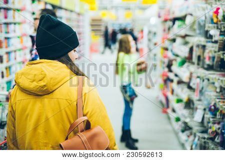 Woman Walk By Mall. Seeking Goods On Shelf Of Store