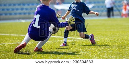 Young Soccer Goalkeeper Save. Boy Catching Soccer Ball. Football Bench And Children Team In The Back