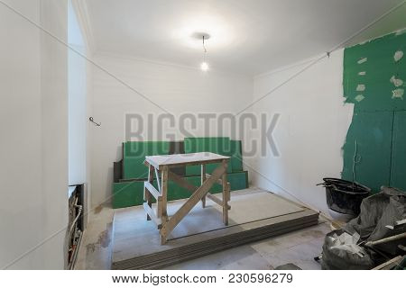 Wooden Board In Room And Sheets Of Plasterboard Or Drywall In An Apartment During On The Constructio