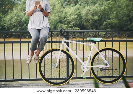Cropped Image Of Young Woman Sitting On Bridge Railing Next To Her Bicycle And Texting