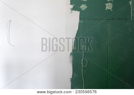 Plasterboard Or Drywall Wall Half Painted With Wires In An Apartment During On The Construction, Rem