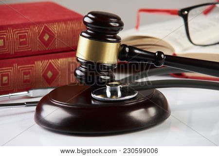 Law Books With Wooden Judges Gavel And Medical Stethoscope On White Table In A Courtroom Or Enforcem