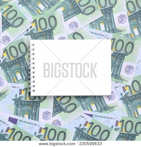 White Notebook With Clean Pages Lying On A Set Of Green Monetary Denominations Of 100 Euros. A Lot O