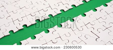 The Green Path Is Laid On The Platform Of A White Folded Jigsaw Puzzle. Texture Image With Copy Spac