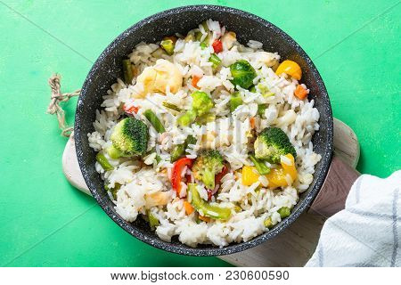Vegetable Risotto In Skillet On Green Table. Rice With Broccoli, Cauliflower, Sweet Pepper And Carro