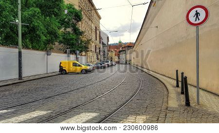 Morning In The Town Along The Narrow Street Parked Cars. Cobblestone Street With Tram Rails.