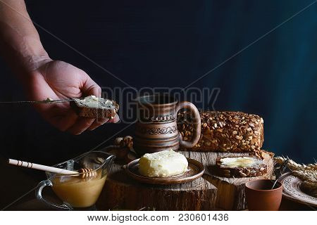 Dark Cereal Bread With Sunflower Seeds Smeared With Butter In Hands, Cup Of Milk, Butter And Honey,