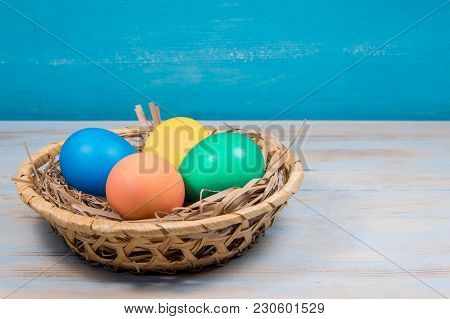 Basket Of Painted In Different Colors Easter Eggs On A Blue Background With A Place For The Inscript