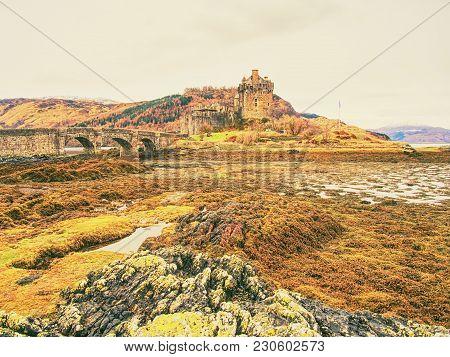 Tides In The Lake At Eilean Donan Castle, Scotland. Bridge Over Dry Sea Algae.