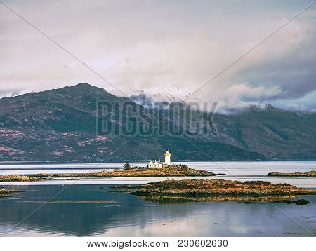 Lighthouse On Isle Of Ornsay, The Southern Side Of Isle Of Skye, Scotland. Trade Ship At Rocky Islan