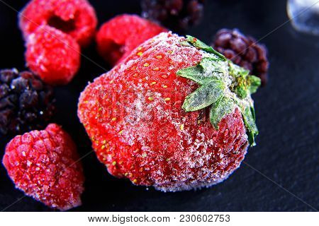 Macro Frozen Raspberry, Berry, Strawberries Mint Leaves, Pieces Of Ice On A Black Shale Board, Froze