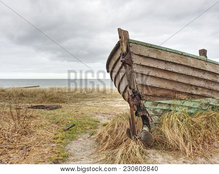 Abandoned Wrecked Boat Stuck In Sand. Old Wooden Boat On The Sandy Shore Of Beach. Sunset On The Bea