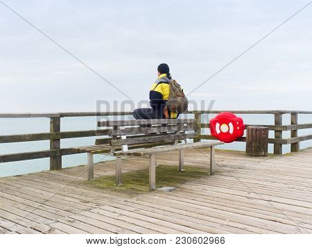 Man In Warm Jacket And Baseball Cap Sit On Wooden Pier And Enjoy Quiet Morning Sea. Tourist Relax.