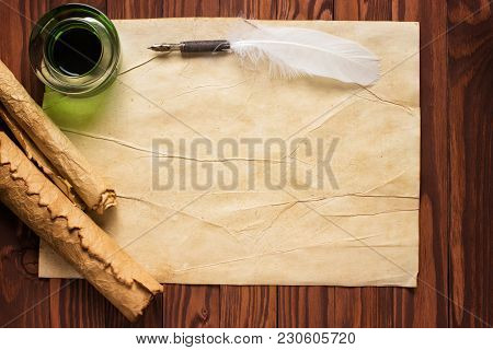 Paper Scroll With Feather Pen And Ink Pot On Wood Background