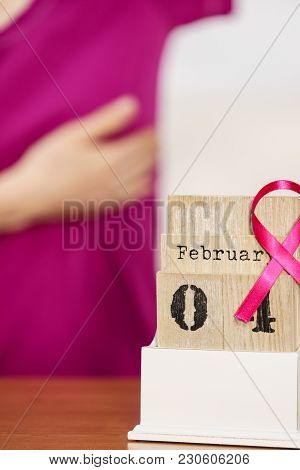 Woman And Calendar, It Is 4 February World Breast Cancer Day, Date With Pink Awareness Ribbon. Healt