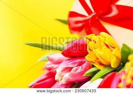 Colorful Tulips Flowers With Decorartive Giftbox On Yellow Background With Free Space. Mothersday Or