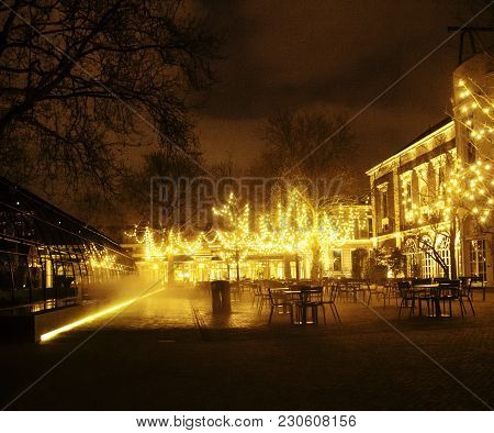 Empty Night Restaurant, Lot Of Tables And Chairs With Noone, Magic Fairy Lights On Trees Like Christ
