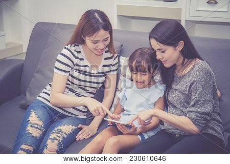 Mother, Aunt And Kid Having Time Together Lerning With Using Tablet At Home With Relax And Happy On