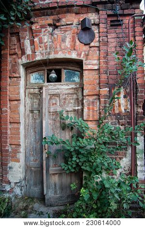 Old Wooden Door Of Red Brick House.