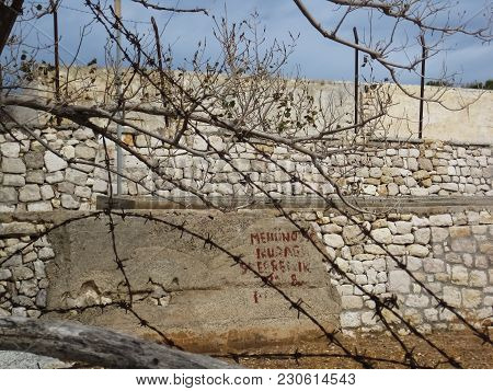 High Wall Made From Stone Built By Political Convicts Judged On Forced Labor And Rusty Metal Wire