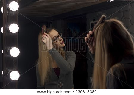 A Woman Combing Her Hair Against The Backdrop Of A Professional Visage Mirror, The Beauty Of Looking