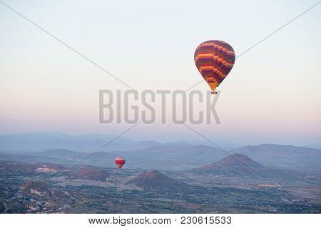 Hot Air Balloons Over Mountain Landscape In Cappadocia, Goreme National Park, Turkey