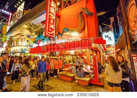Osaka, Japan - April 29, 2017: Tourists Walk The Streets Of Namba District By Night With Various Foo
