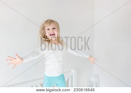 Happy Kid Jumping Over Bed. Cute Little Blond Girl Having Fun Indoors. Happy And Careless Childhood