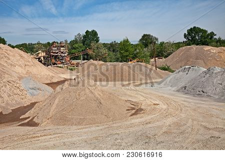 Sand And Gravel Pit With Mounds Of Extracted Material And Convoyer