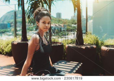 Young Cutesmiling Afro American Girl In A Black Dress Is Sitting On A Wooden Bench Of The Top-floor