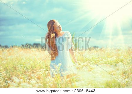 Beauty Girl Outdoor enjoying nature. Beautiful Model with long hair in white dress having fun on summer Field with blooming flowers, Sun Light. Free Happy Woman on spring meadow, countryside