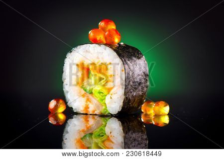 Sushi roll japanese food over black background. Sushi roll with tuna, vegetables, flying fish roe and caviar closeup. Japan restaurant menu