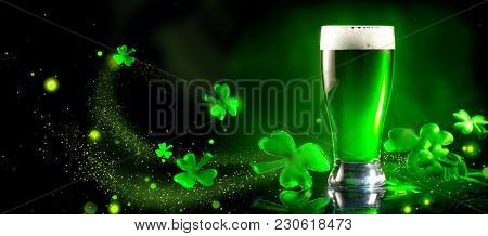 St. Patric's Day Green Beer pint over dark green background, decorated with shamrock leaves. Patric Day pub party, celebrating. Glass of Green beer close-up. Border art design, Wide format banner