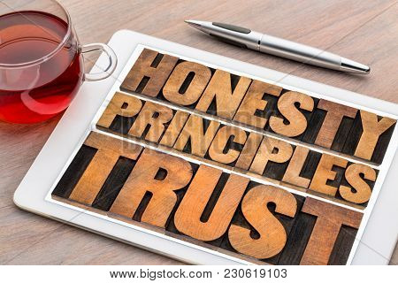 honesty, principles and trust concept - word abstract in vintage letterpress wood type on a digital tablet with a cup of tea