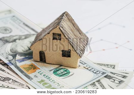 Ceramic House On Pile Of Us Dollar Banknotes With Printed Price Chart, House Or Real Estate Buy, Sel