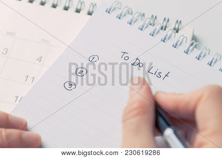 Female Hand Holding Black Pen Writing To Do List Prioritized By Number On White Paper Notepad With D