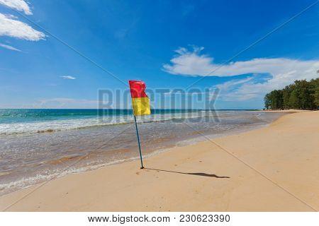 Red yellow warning flag at beach. Phuket, Thailand.