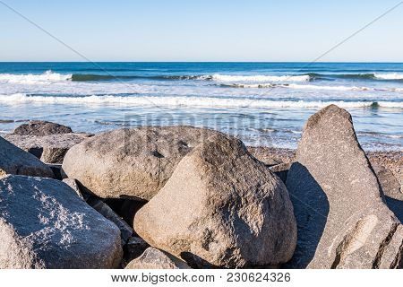 Large Boulders On South Carlsbad State Beach In San Diego, California With Waves In The Background.