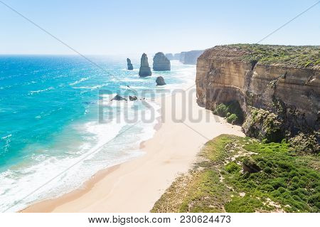 Twelve Apostels With Beach And Grass And Backlight At The Great Ocean Road, Victoria, Australia