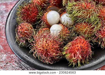 Rambutans On The Wet Black Plate On The Shabby Wooden Red Table. Closeup Horizontal Photo.