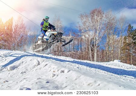 Sport White Snowmobile Jump. Clear Sunny Winter Day. Concept Quick Movement. Extreme Sport Backgroun
