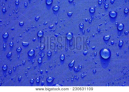 Close Up Water Drops Pattern Over A Blue Waterproof Cloth Background. World Water Day Concept.