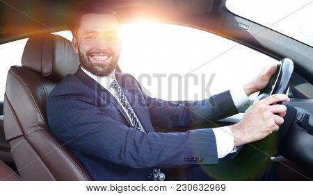 portrait of confident businessman driving a car