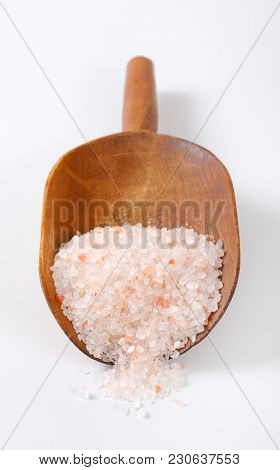 scoop of coarse grained salt on white background