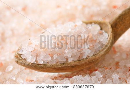 spoon of coarse grained salt on coarse grained salt background - detail
