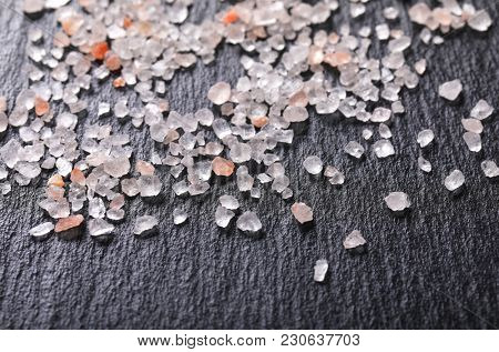 crystals of coarse grained salt on black background - close up