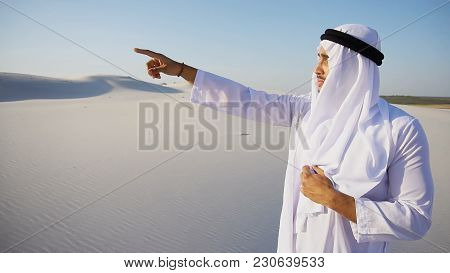 Serious Young Arabian Uae Sheikh Man Peers Into Distance And Tries To See Caravan Of Camels Walking,