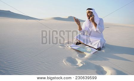 Handsome Arabian Uae Sheikh Male Businessman Talks On Mobile With Business Partner And Solves Import