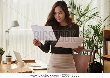 Smiling Eautiful Business Woman Comparing Information In Two Documents
